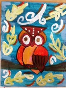 Orange Owl  with hanging leaves in background